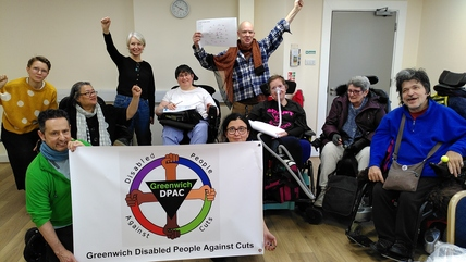 Photo of GDPAC members with their banner, celebrating the session with hands in the air